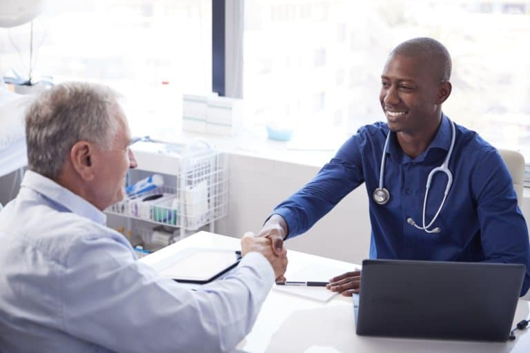 Senior Male Patient Shaking Hands With Doctor Sitting At Desk In Office